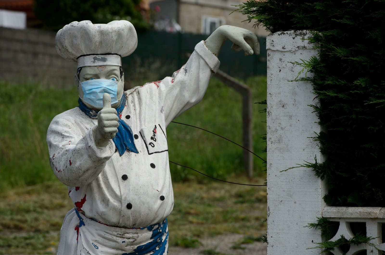 A statue of a cook wearing a face mask is pictured outside a restaurant in Vigo, on May 10, 2020 during the national lockdown to prevent the spread of the COVID-19 disease. (AFP Photo)