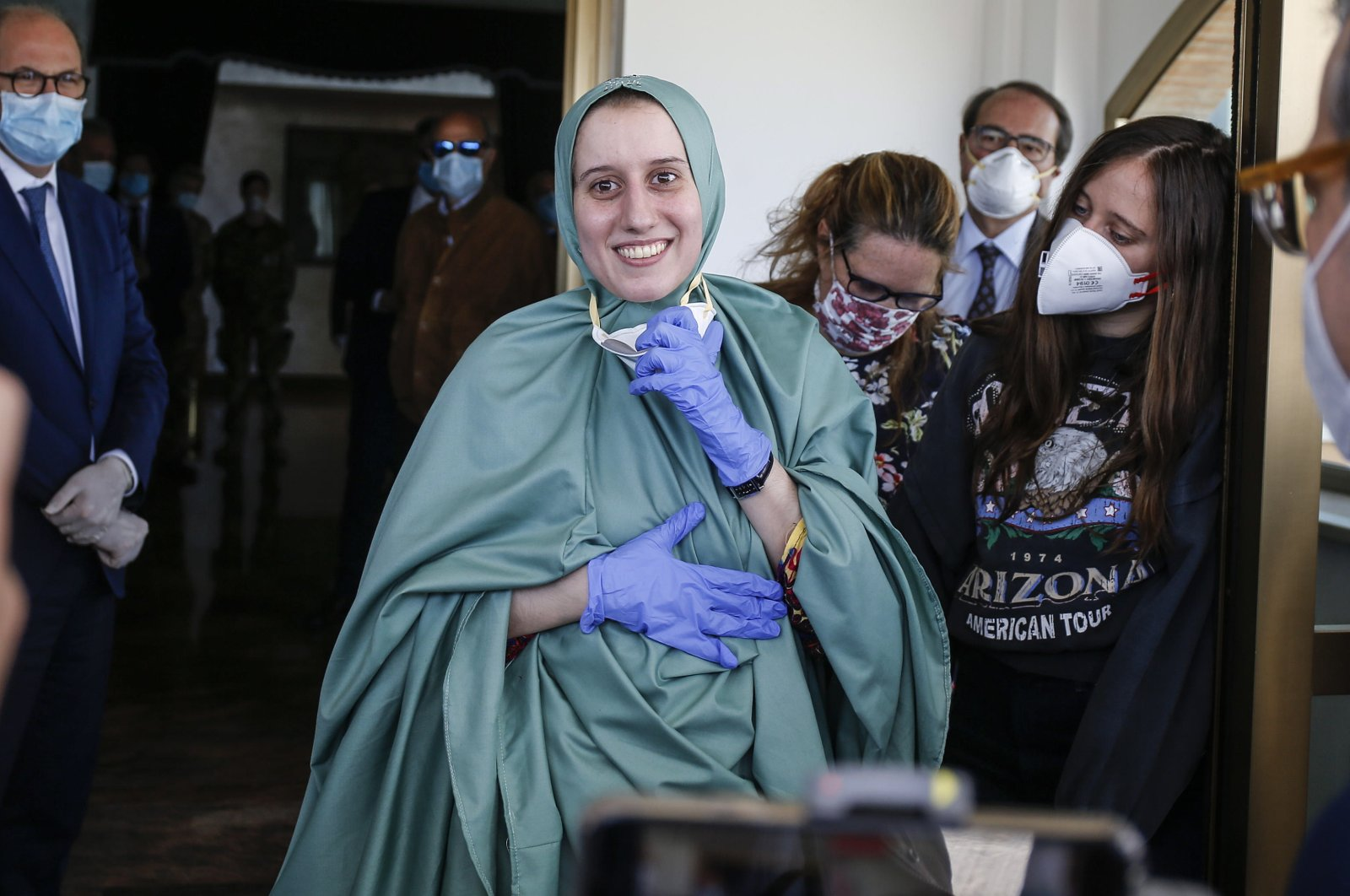 Silvia Romano, wearing a green tunic, reacts upon her arrival at the Ciampino airport, Rome, Italy, May 10, 2020. (EPA Photo)