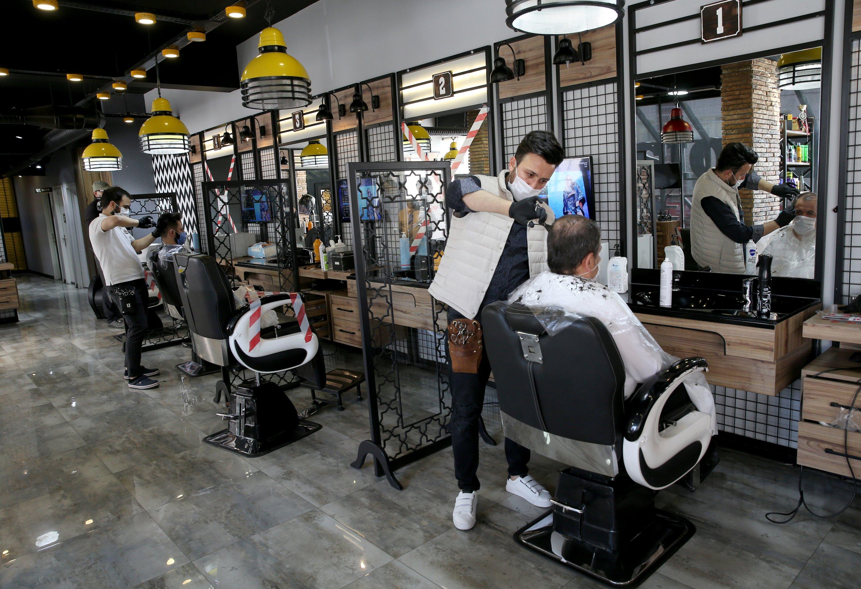 Barbers cut their customers' hair in a barbershop in the capital Ankara, Turkey, May 11, 2020. (AA Photo)