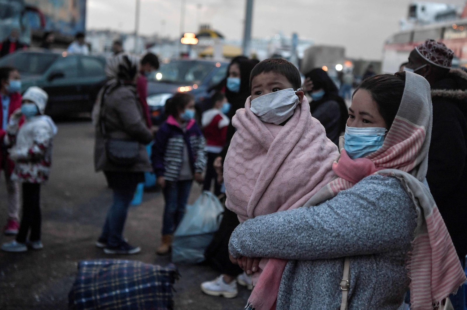 A woman holds her child as migrants transferred from the Moria camp on the island of Lesbos disembark in the port of Piraeus near Athens, May 4, 2020. (AFP Photo)