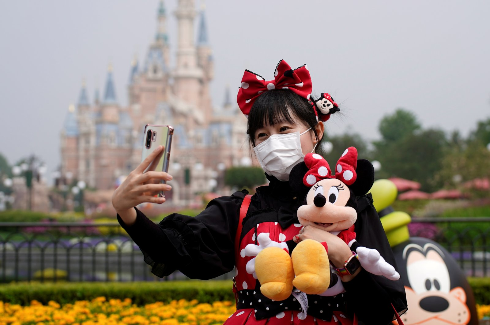 A visitor dressed as a Disney character takes a selfie while wearing a protective face mask at Shanghai Disney Resort as the Shanghai Disneyland theme park reopens following a shutdown due to the coronavirus outbreak, in Shanghai, China, May 11, 2020. (Reuters Photo)