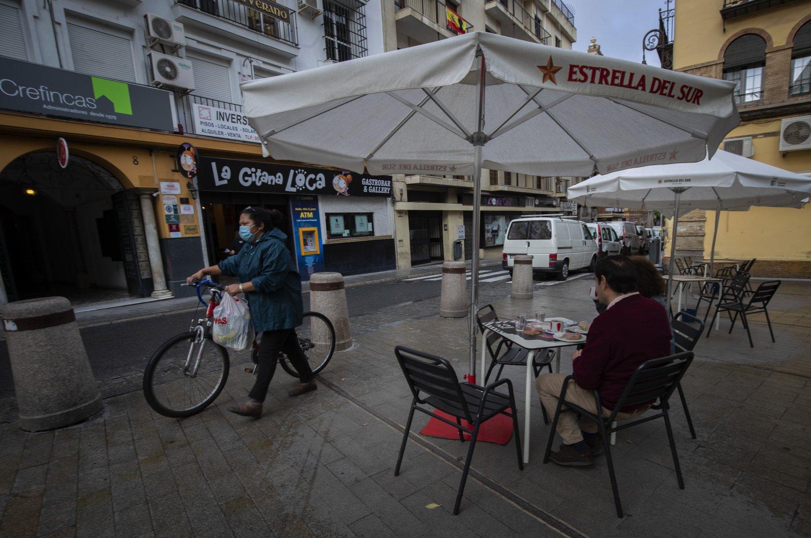Two people eat breakfast in a terrace bar, Seville, Spain, May 11, 2020. (AP Photo)