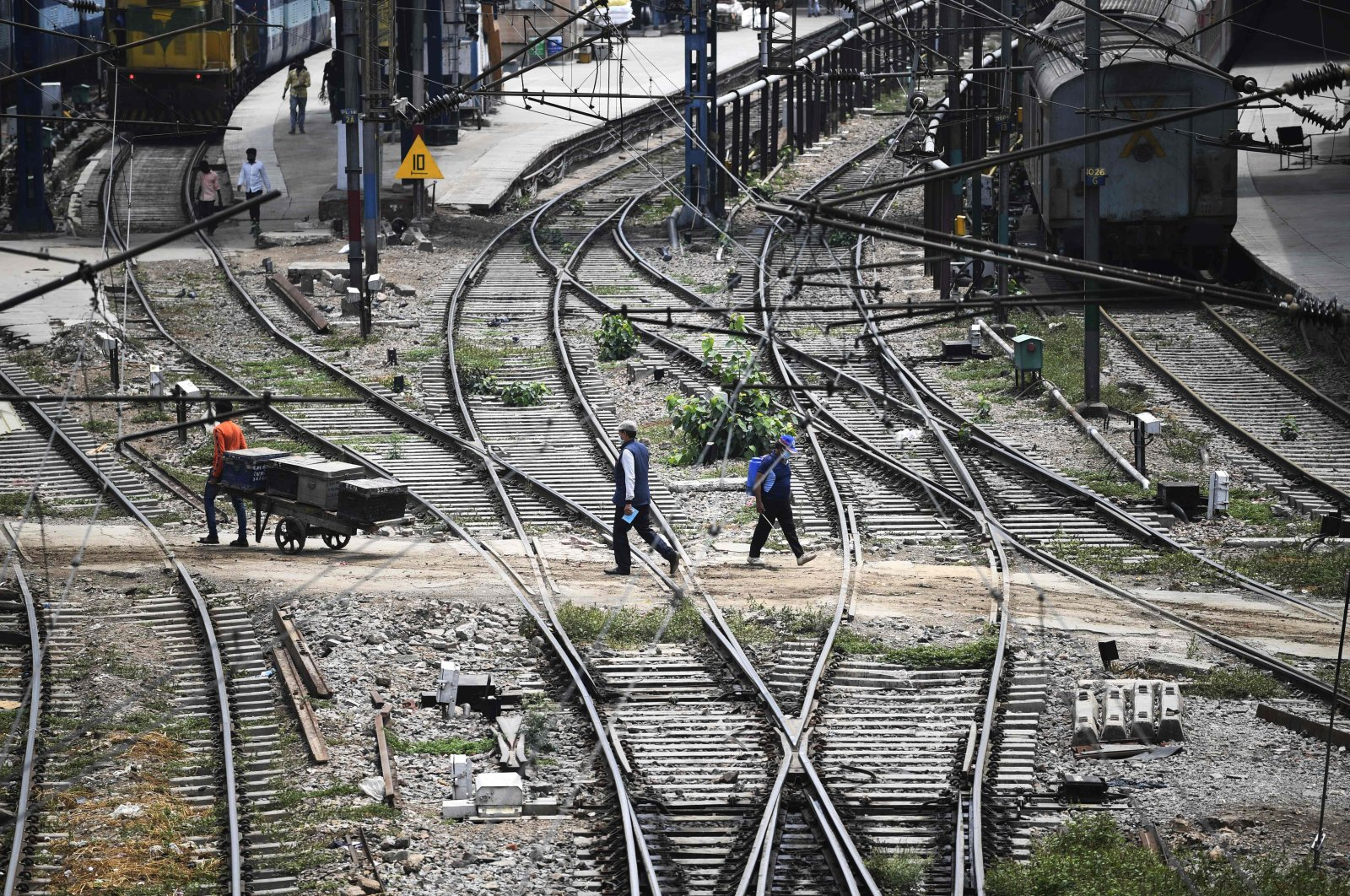Commuters walk through the tracks at the railway station in New Delhi on May 11, 2020. (AFP Photo)
