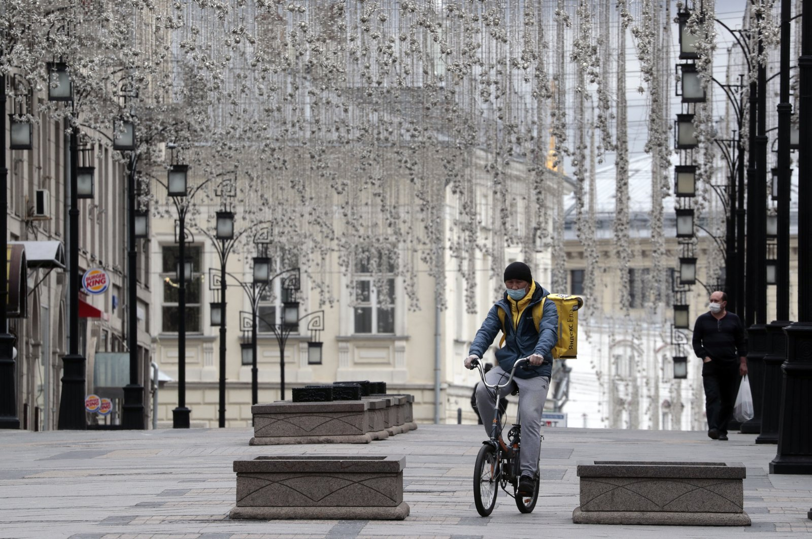 A food courier bikes to his client along a deserted street, Moscow, Russia, May 8, 2020. (EPA Photo)
