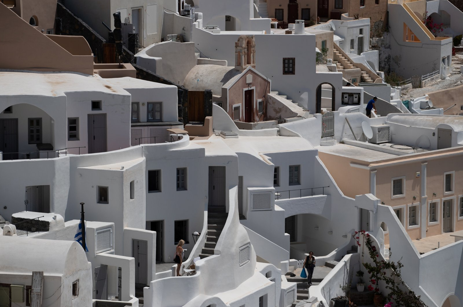 Locals make their way in deserted Oia, a popular touristic hotspot before the coronavirus outbreak, on the island of Santorini, Greece, May 7, 2020. (Reuters Photo)