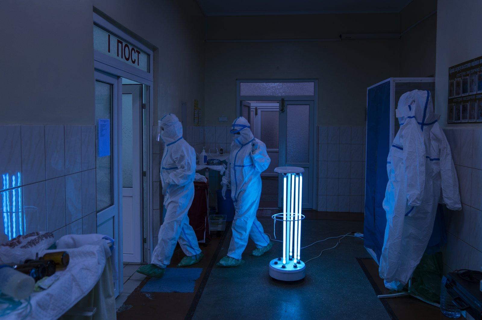 Medical specialists wearing special suits to protect against the coronavirus walk through a disinfectant corridor toward the intensive care unit at a regional hospital in Chernivtsi, Ukraine, May 4, 2020. (AP Photo)