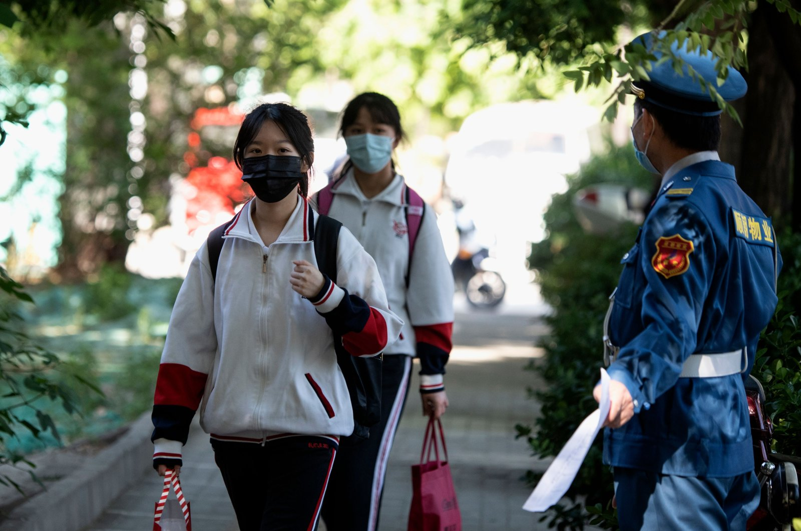 Students wearing face masks over concerns about the coronavirus arrive at a middle school in Beijing, China, May 11, 2020. (AFP Photo)