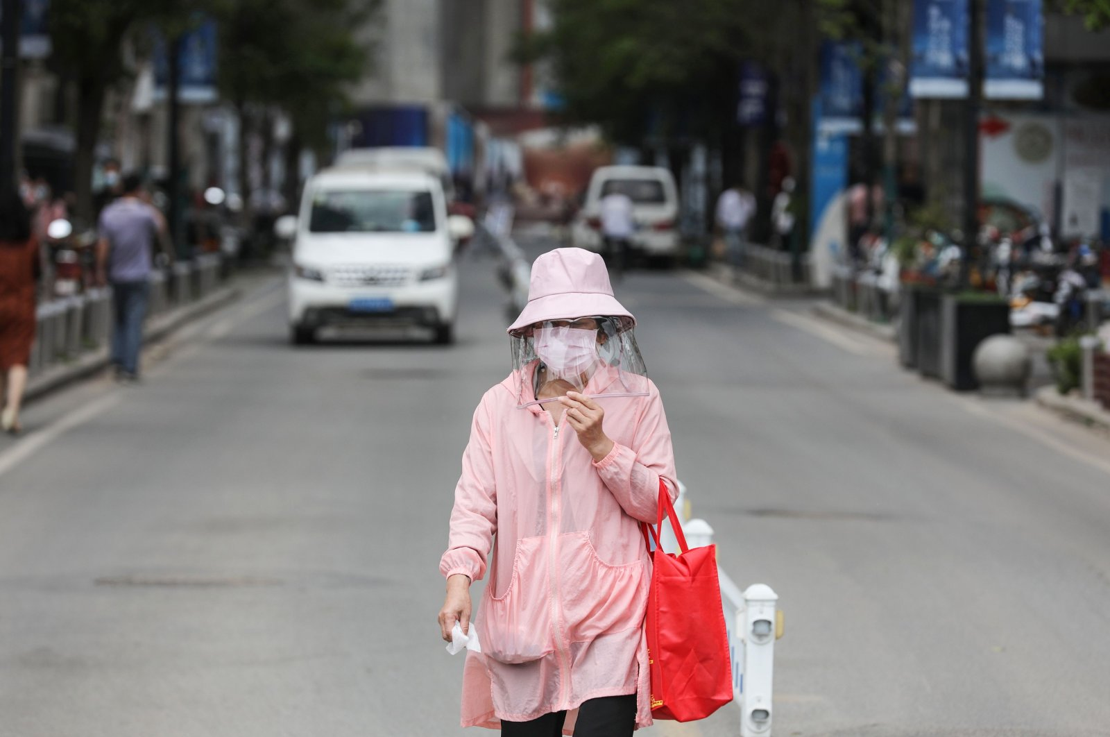 A woman wears a face shield as she walks along a street, Wuhan, China, May 11, 2020. (AFP Photo)