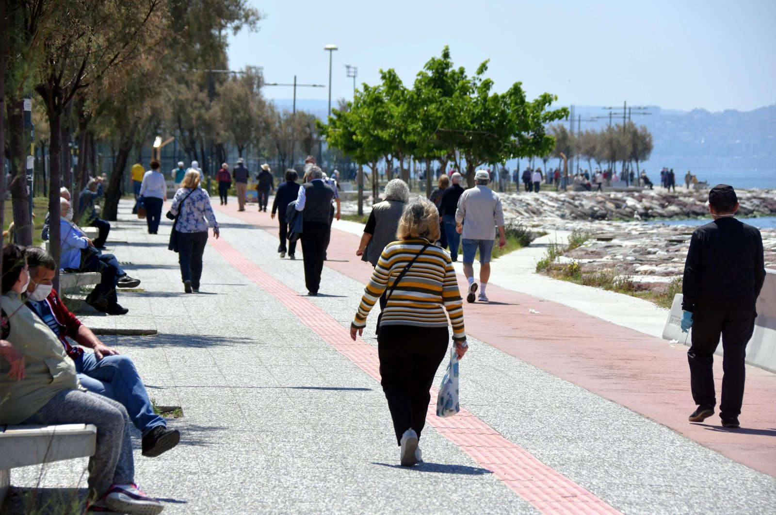 Senior citizens go for a stroll in Izmir's Karşıyaka after the curfew was temporarily lifted, May 10, 2020 (DHA Photo)