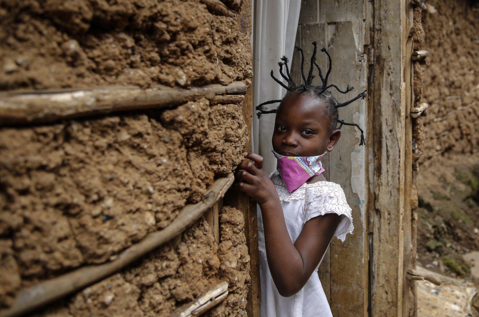 Jane Mbone, 7, arrives home after having her hair styled in the shape of the new coronavirus at the Mama Brayo Beauty Salon in the Kibera slum, or informal settlement, in Nairobi, Kenya, May 3, 2020. (AP Photo)