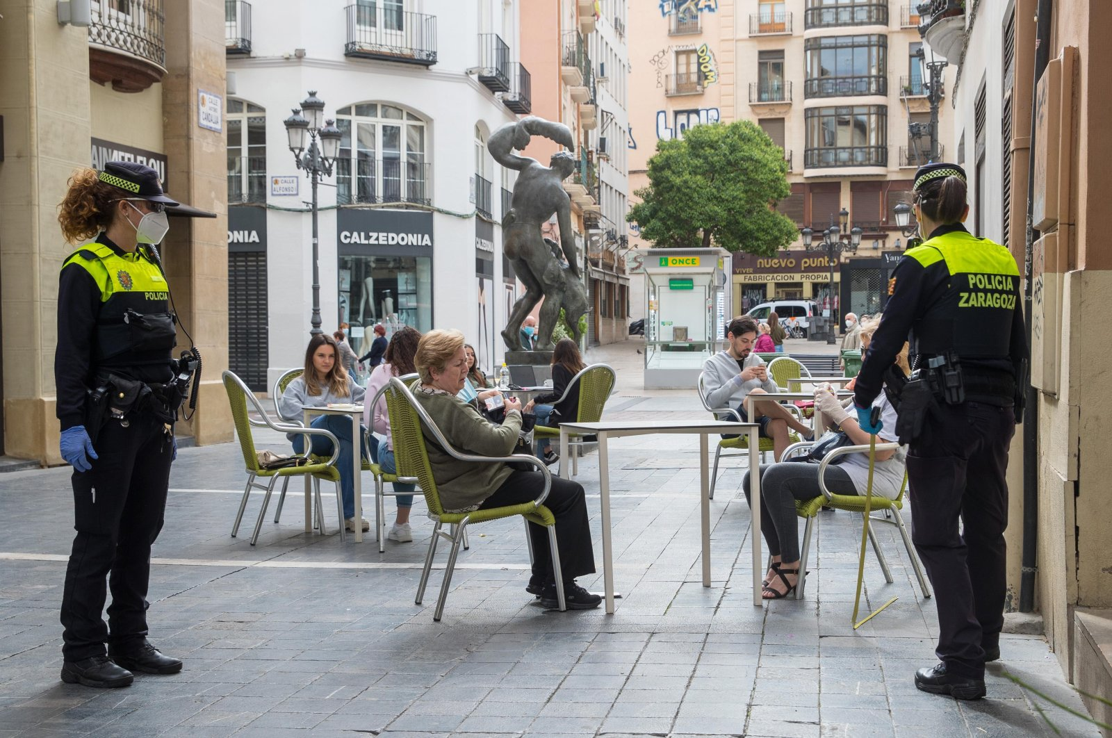 Police measure distance between tables at a bar terrace in downtown in Zaragoza, May 11, 2020. (EPA Photo)