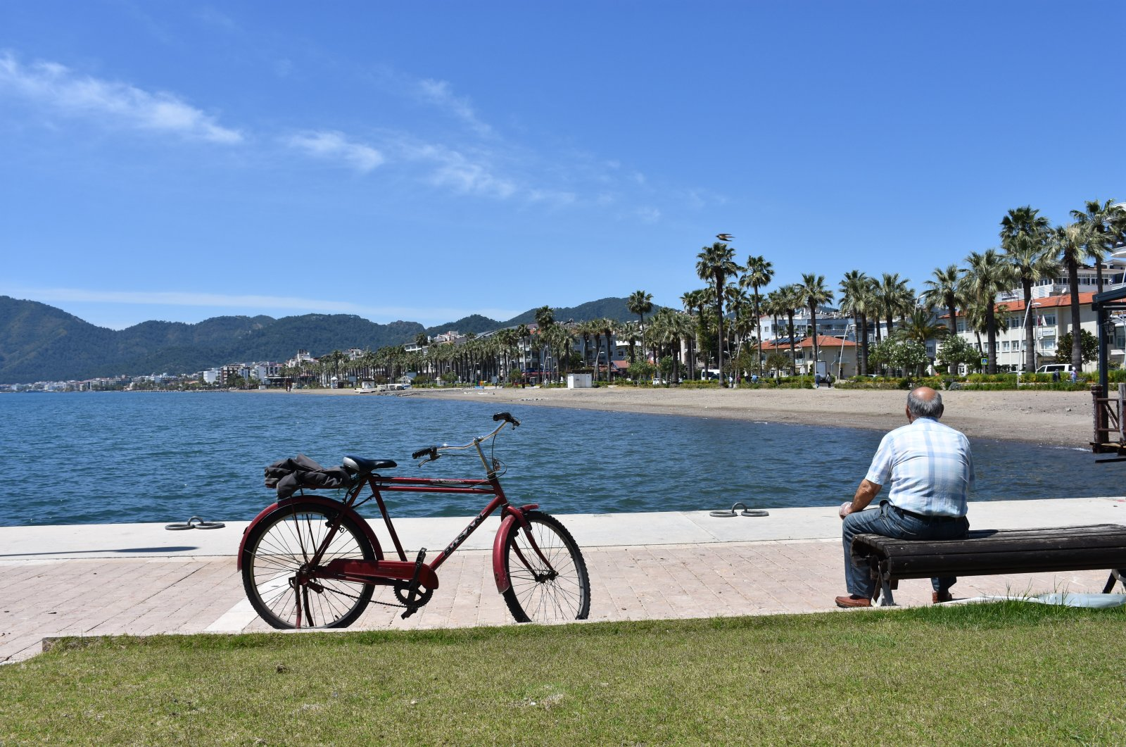 A man sits on a bench next to the shore on a sunny day in the resort town of Muğla, Turkey, May 10, 2020. (AA Photo)