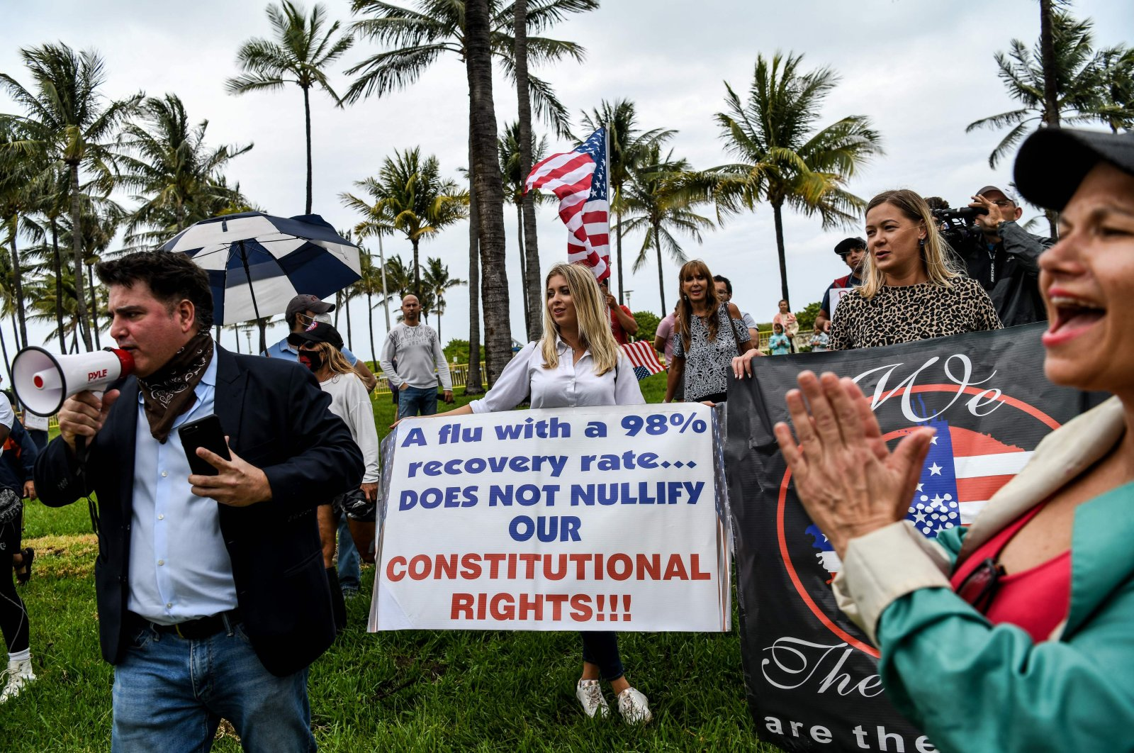 """Protestors hold placards, wave the American flag and shout slogans as they participate in a """"Freedom Rally"""" protest in support of reopening Florida, South Beach, Miami, May 10, 2020. (AFP Photo)"""
