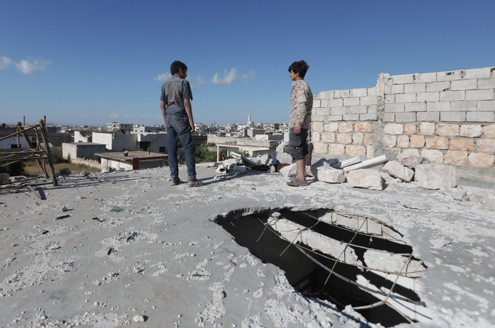 Syrian youths stand on May 6, 2020 on the damaged roof of a building in al-Nayrab, a town ravaged by pro-Assad forces' bombardment near the M4 strategic highway, in Syria's northwestern Idlib province (AFP Photo)