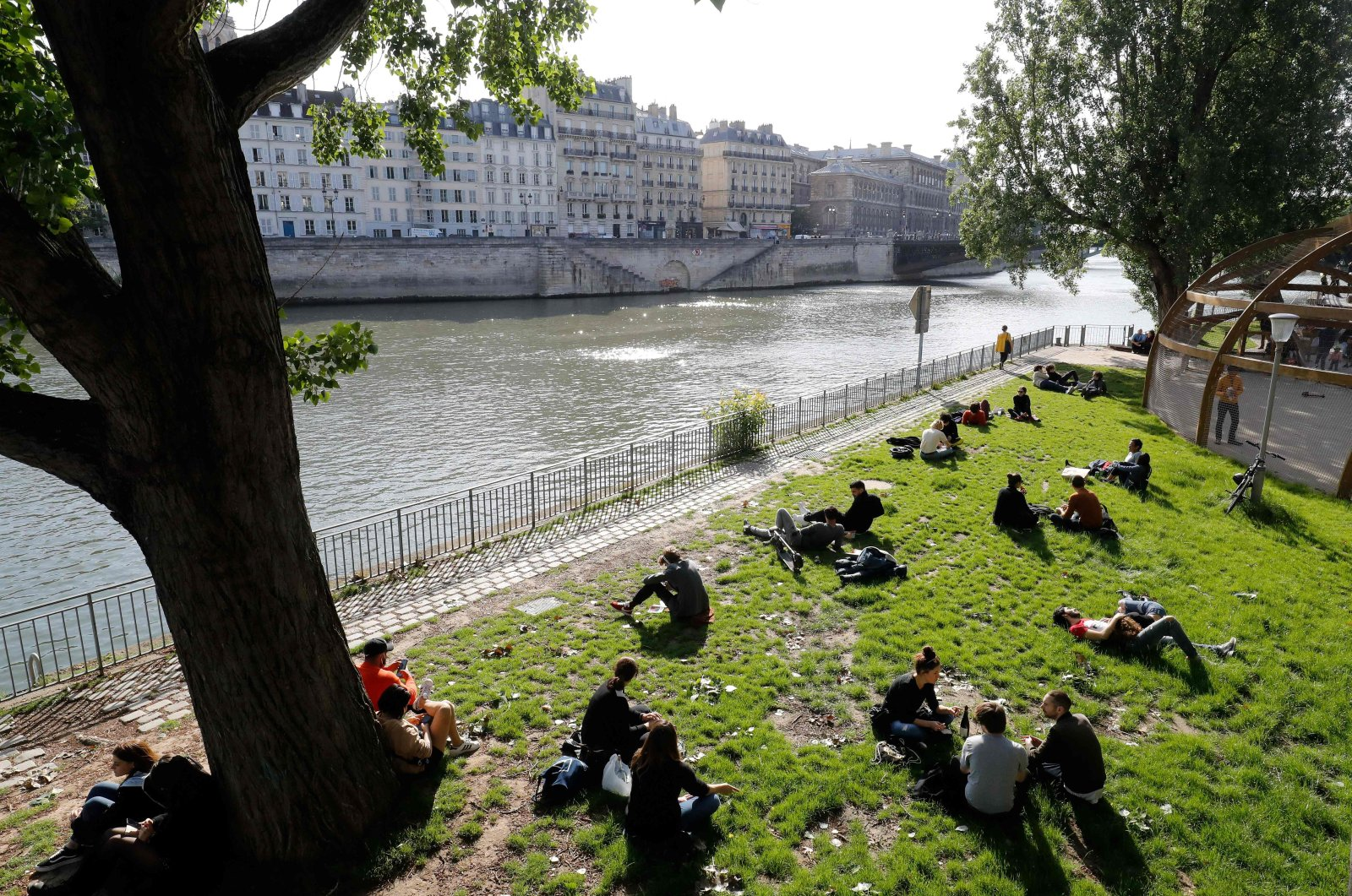People gather along banks of the Seine river in Paris, on May 11, 2020, on the first day of France's easing of lockdown measures in place for 55 days to curb the spread of the COVID-19 pandemic, caused by the novel coronavirus. (AFP Photo)