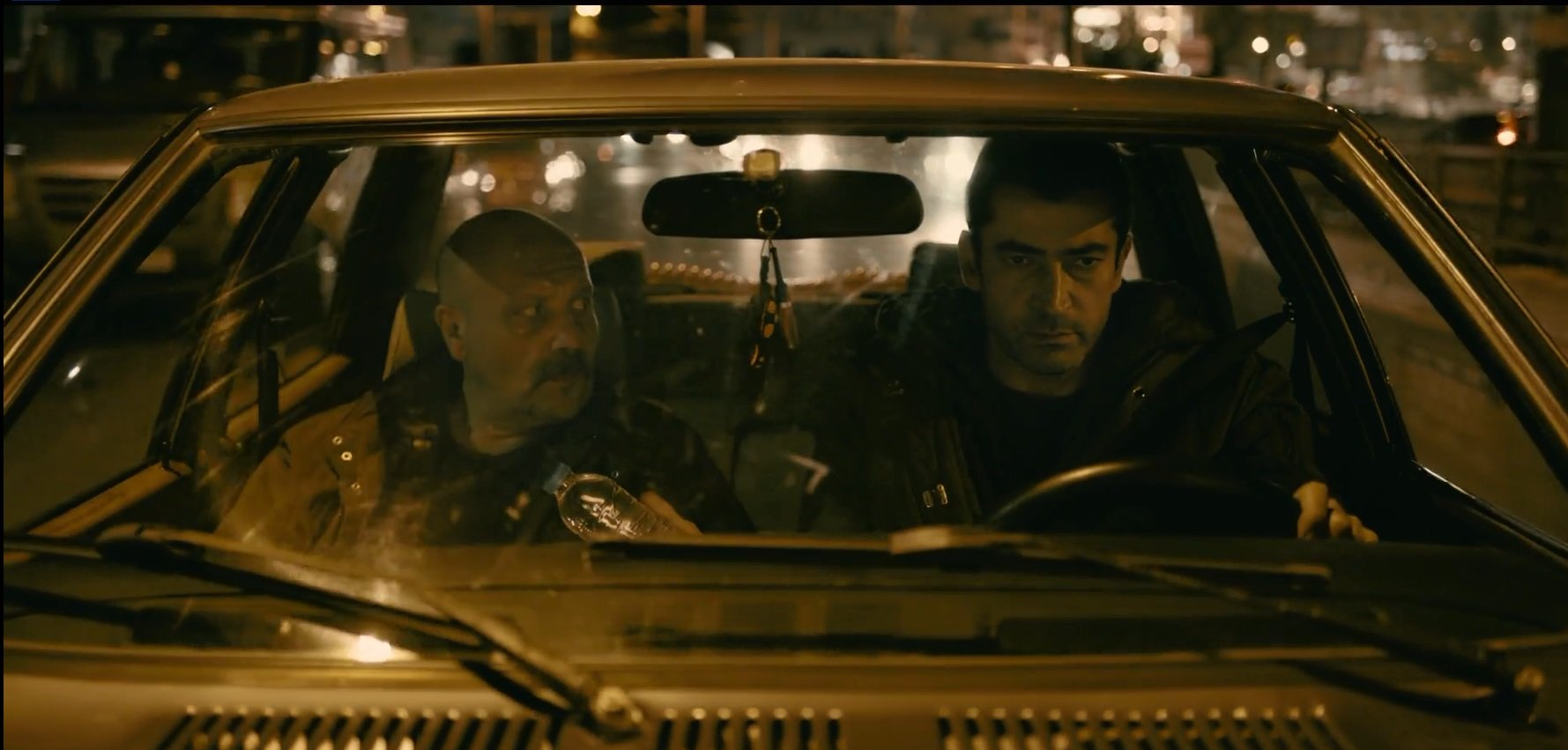 A still from the series showing detective Settar (L) and Kemal in a car.