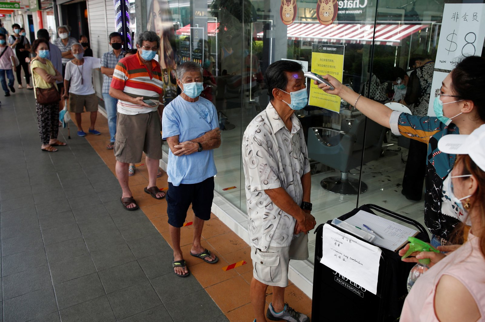 Customers queue up to have their temperature taken outside a hairdressing salon as they reopen for business amid the coronavirus disease (COVID-19) outbreak in Singapore May 12, 2020. (Reuters Photo)