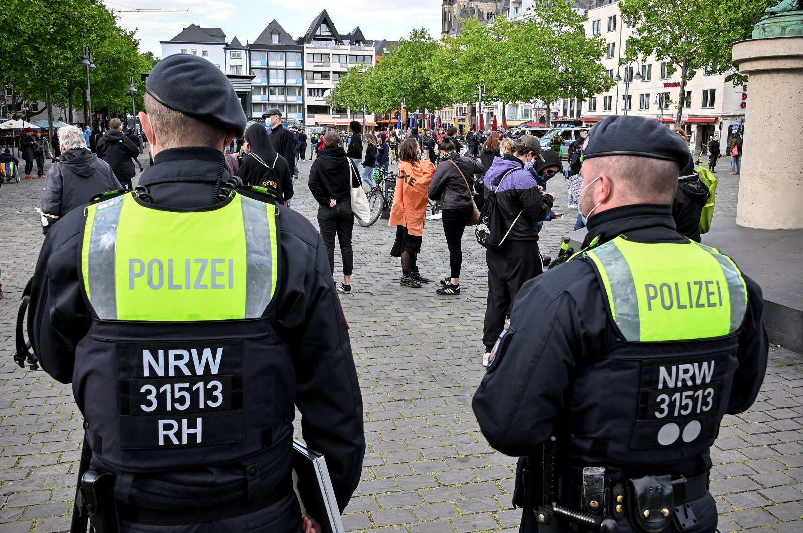 Police officers observe demonstrators during a gathering on the Heumarkt in Cologne, Germany, 11 May 2020. (EPA Photo)