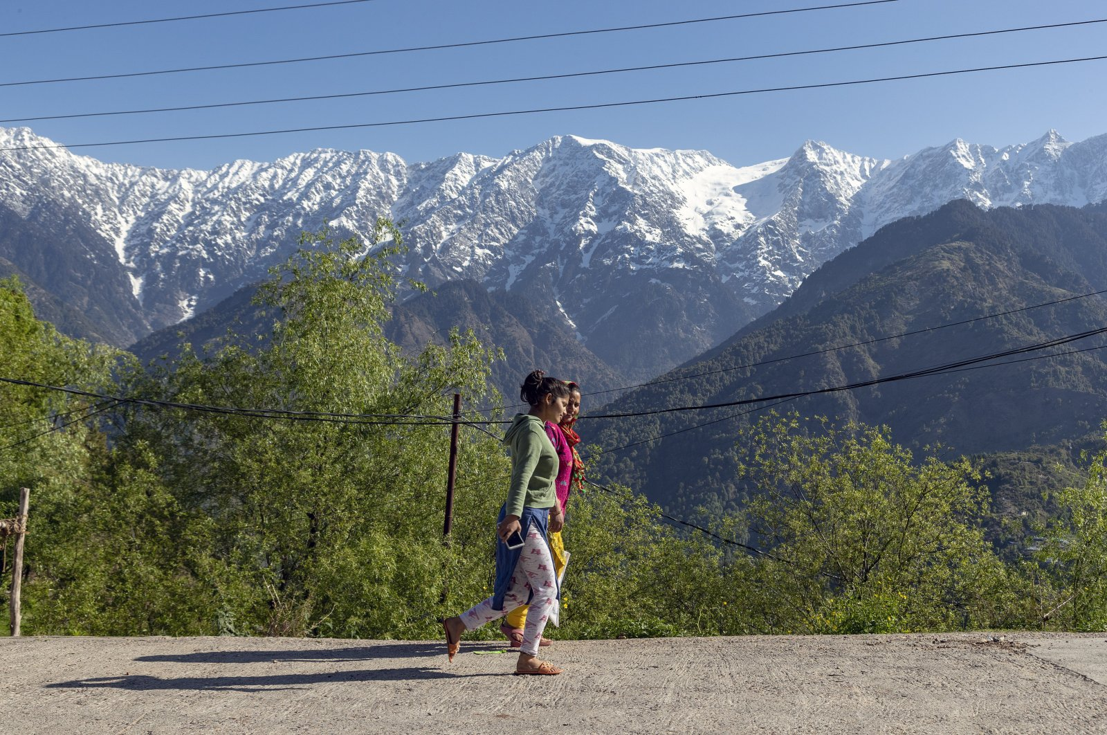 Women walk against a backdrop of the snow-covered Dhauladhar range of the Himalayas during relaxation in the curfew imposed to check the spread of the coronavirus in Dharmsala, India, April 19, 2020. (AP Photo/Ashwini Bhatia)