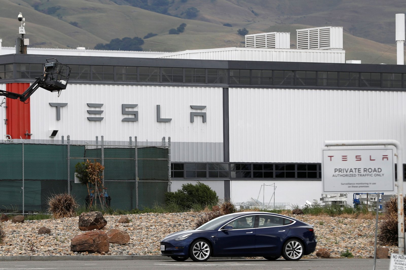 A Tesla vehicle drives past Tesla's primary vehicle factory after CEO Elon Musk announced he was defying local officials' coronavirus disease (COVID-19) restrictions by reopening the plant in Fremont, California, U.S. May 11, 2020. (Reuters Photo)