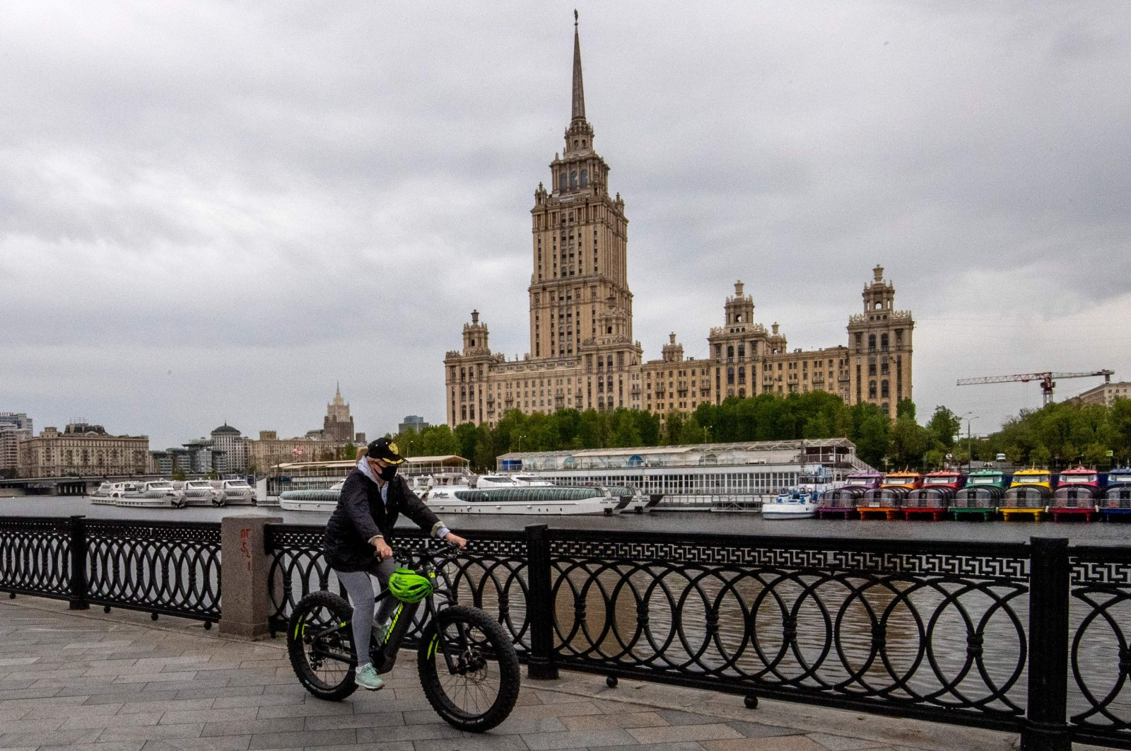 A woman wears a protective face mask as she rides a bike along the Moskva river embankment, Moscow, May 10, 2020. (AFP Photo)