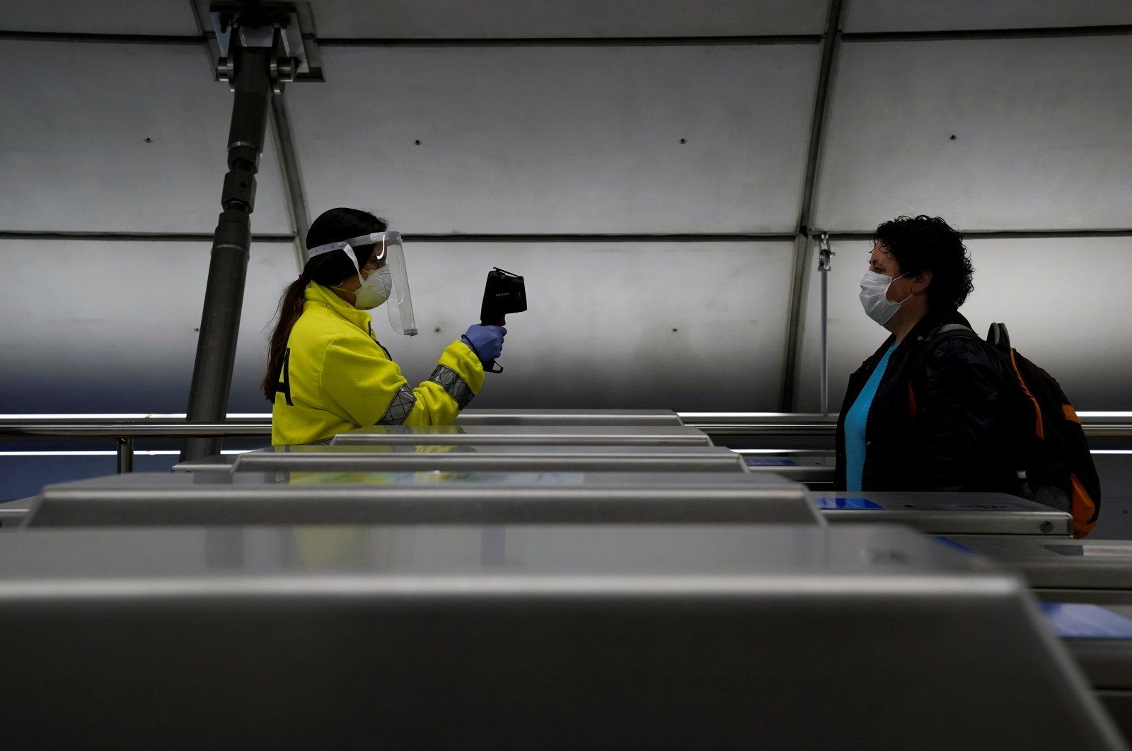 A member of the voluntary ambulance service organisation DYA (Detente y Ayuda) uses a thermal imaging camera to take the temperature of a train passenger in Bilbao, Spain, May 11, 2020. (Reuters Photo)