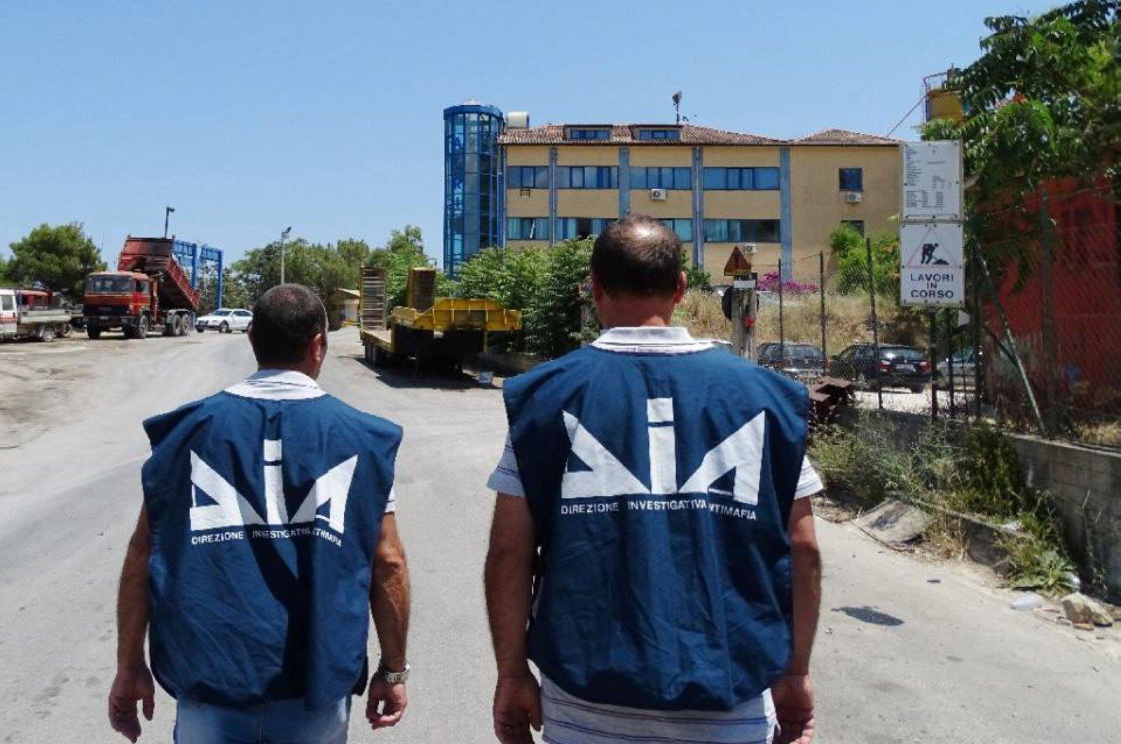 Anti-mafia department (DIA) police officers walk near a seized firm, Palermo. (File Photo)