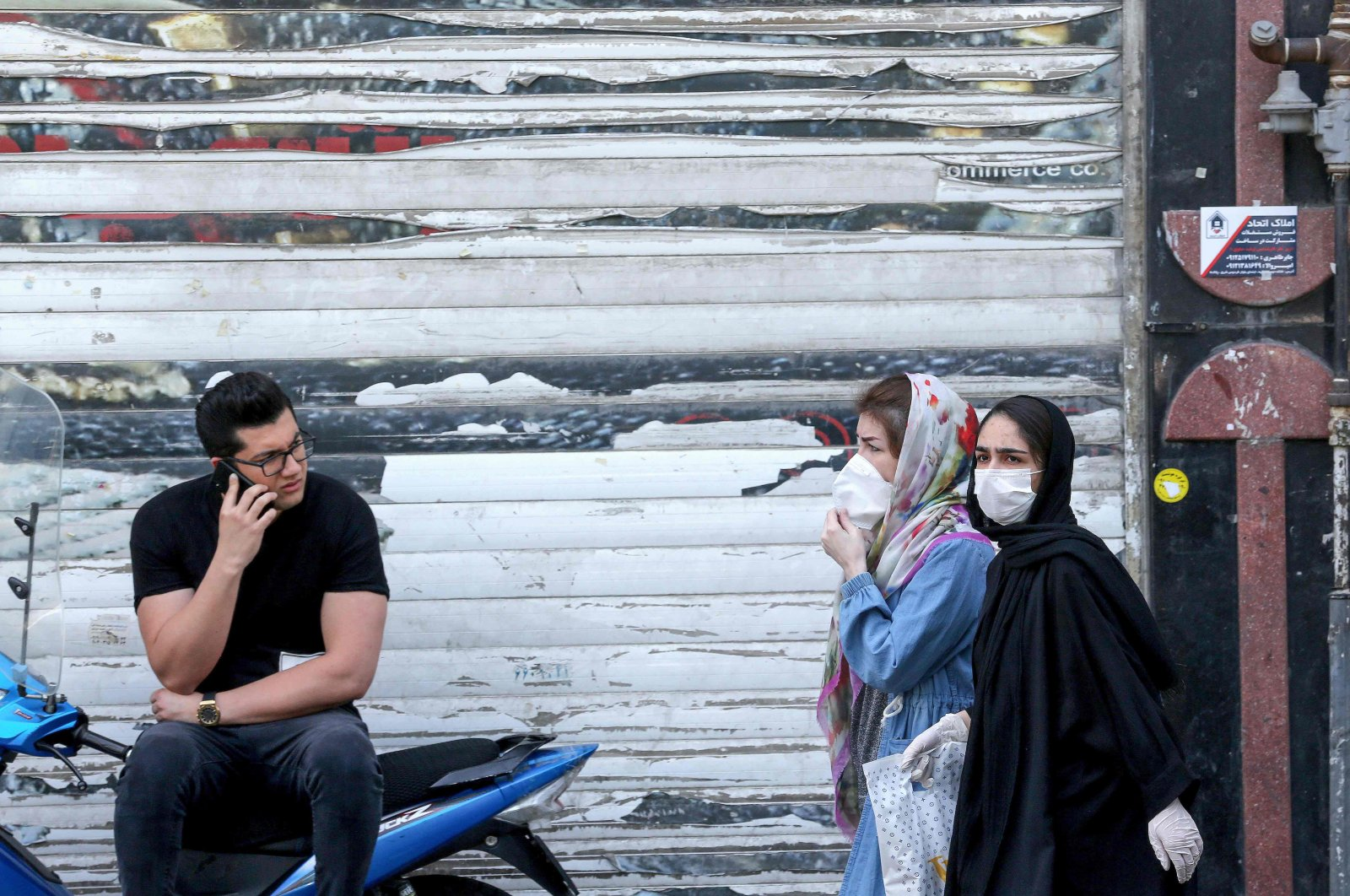 An Iranian youth talks on the phone as he watches women wearing protective masks walk by on a street of the capital Tehran, May 9, 2020. (AFP)
