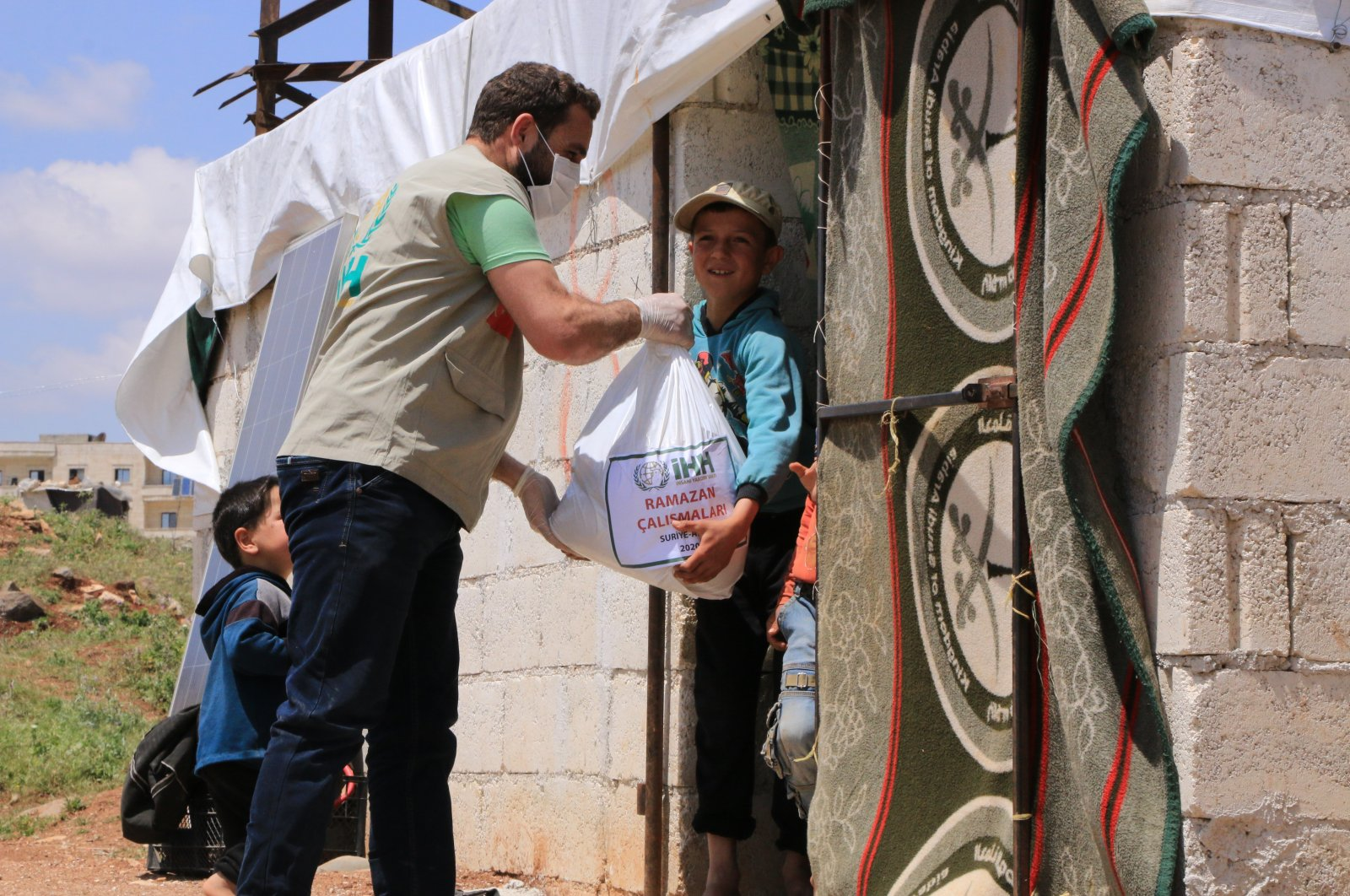 A İHH worker distributes aid to families in northwestern Syria's Afrin, May 12, 2020. (AA Photo)