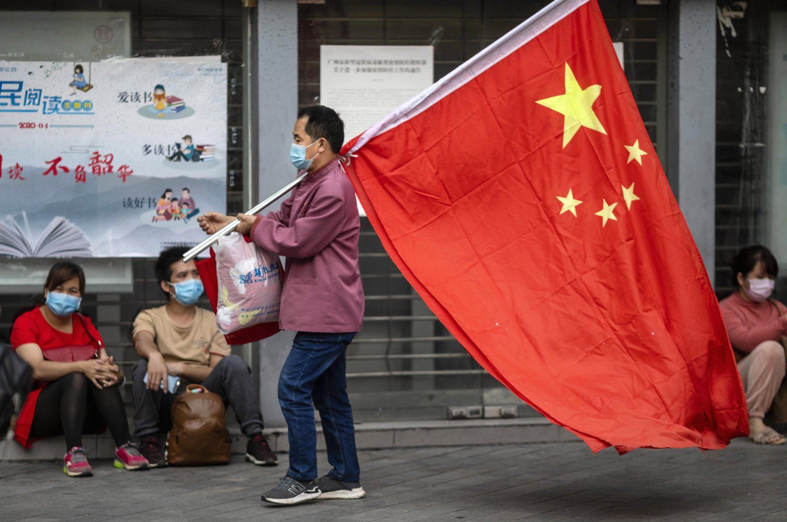 A man wearing a mask and carrying a Chinese flag walks on the street in Guangzhou, Guangdong province, China, April 28, 2020. (EPA Photo)