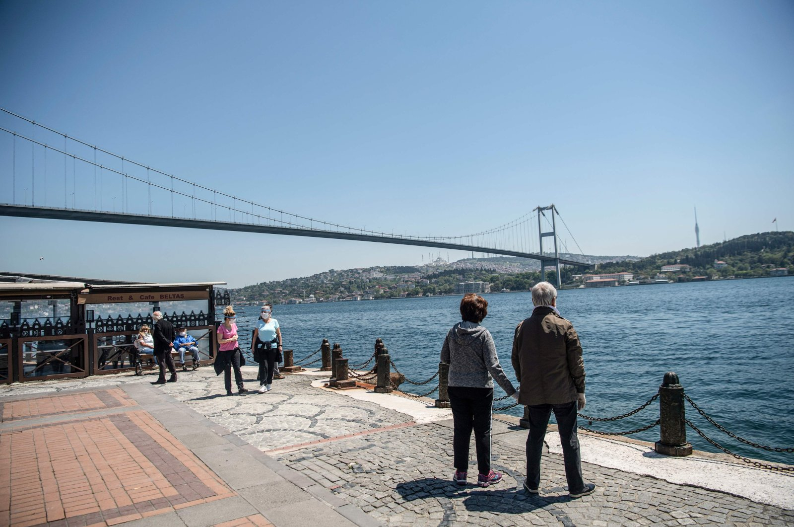 An elderly couple wearing protective face masks looks out toward the July 15 Martyrs' Bridge in the Ortaköy neighborhood of Istanbul, Turkey, May 10, 2020. (AFP Photo)