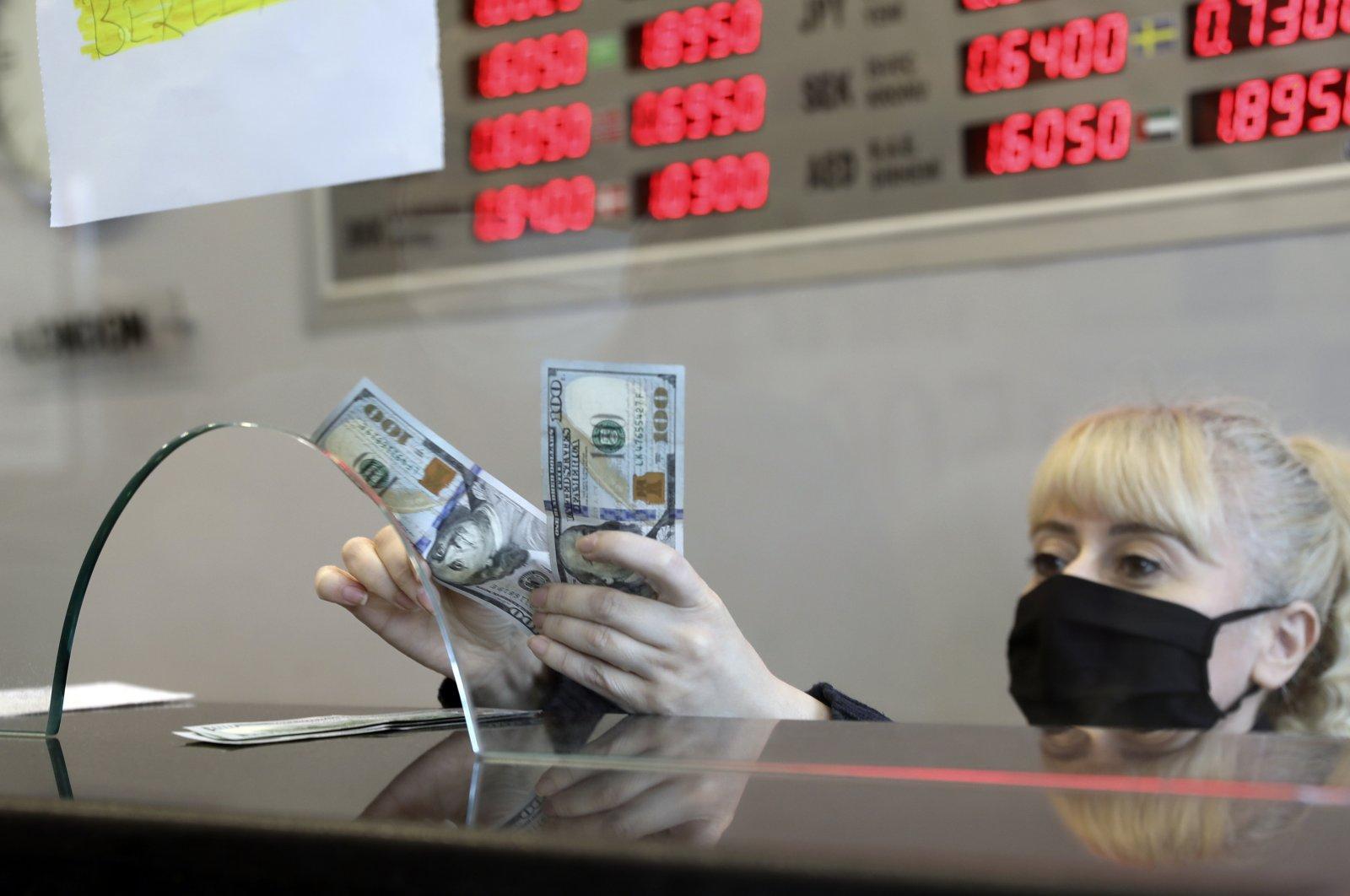 An official wearing a face mask for protection against the coronavirus exchanges a customer's Turkish liras for U.S. dollars at a currency exchange office, Ankara, Turkey, May 8, 2020. (AP Photo)