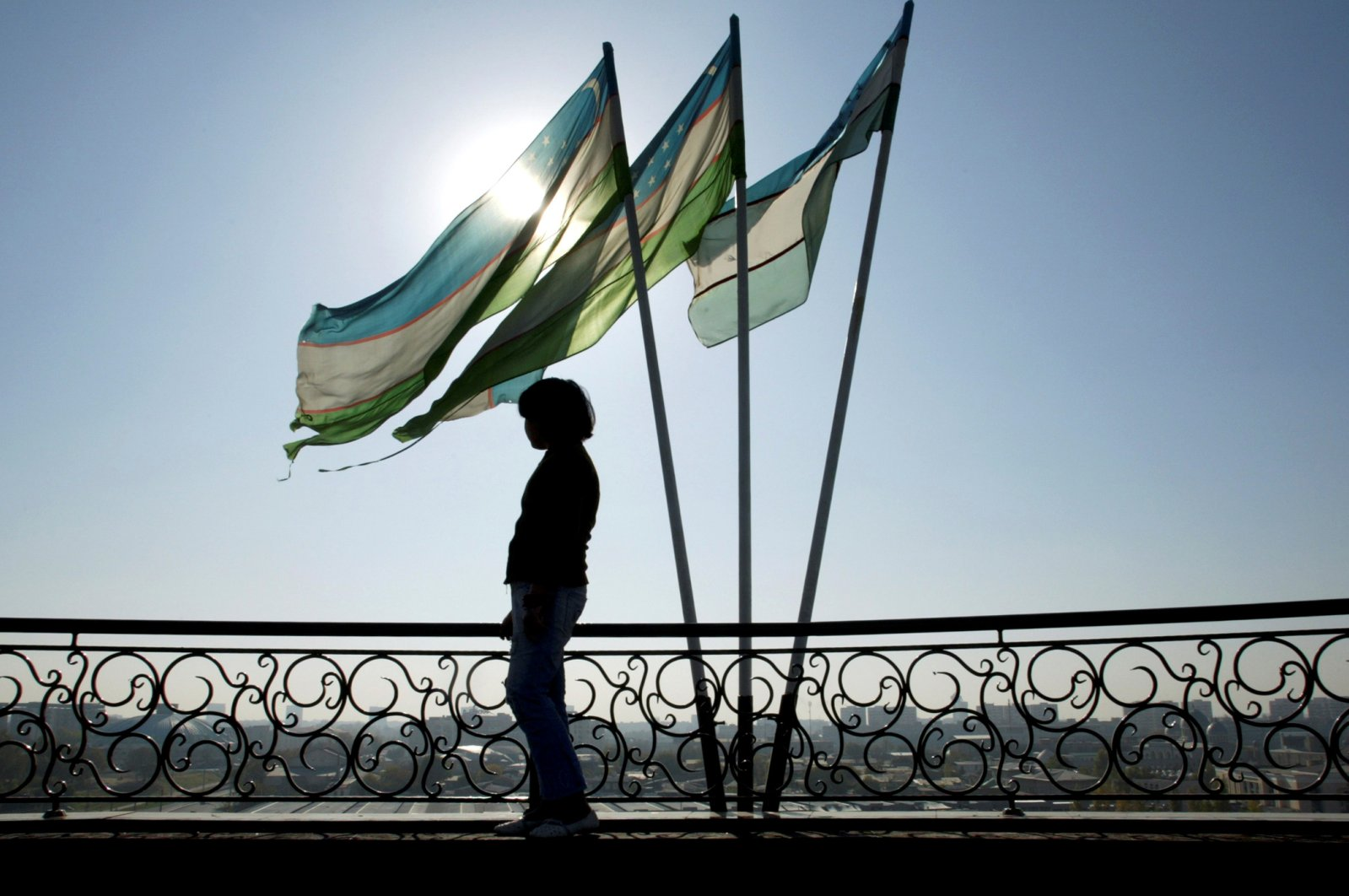 A girl is silhouetted against the sun standing next to Uzbek flags in Tashkent. (Reuters Photo)