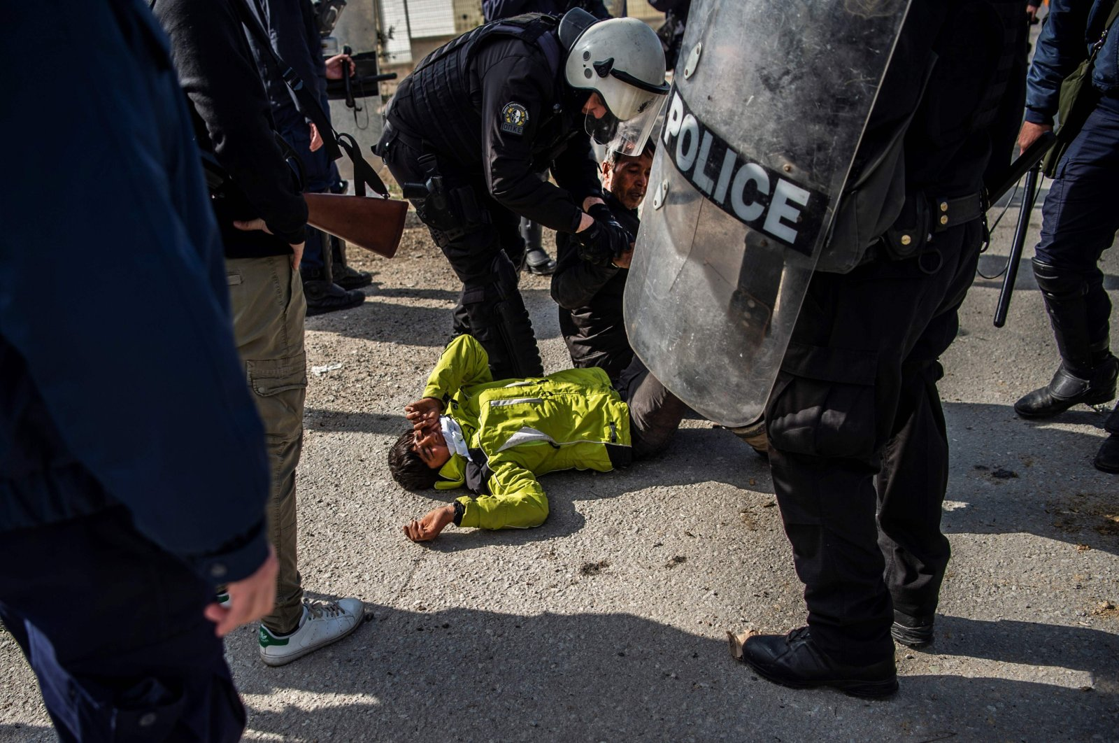 Riot police detain a migrant during clashes near the Moria camp for refugees and migrants, on the island of Lesbos, Greece, March 2, 2020. (AFP Photo)