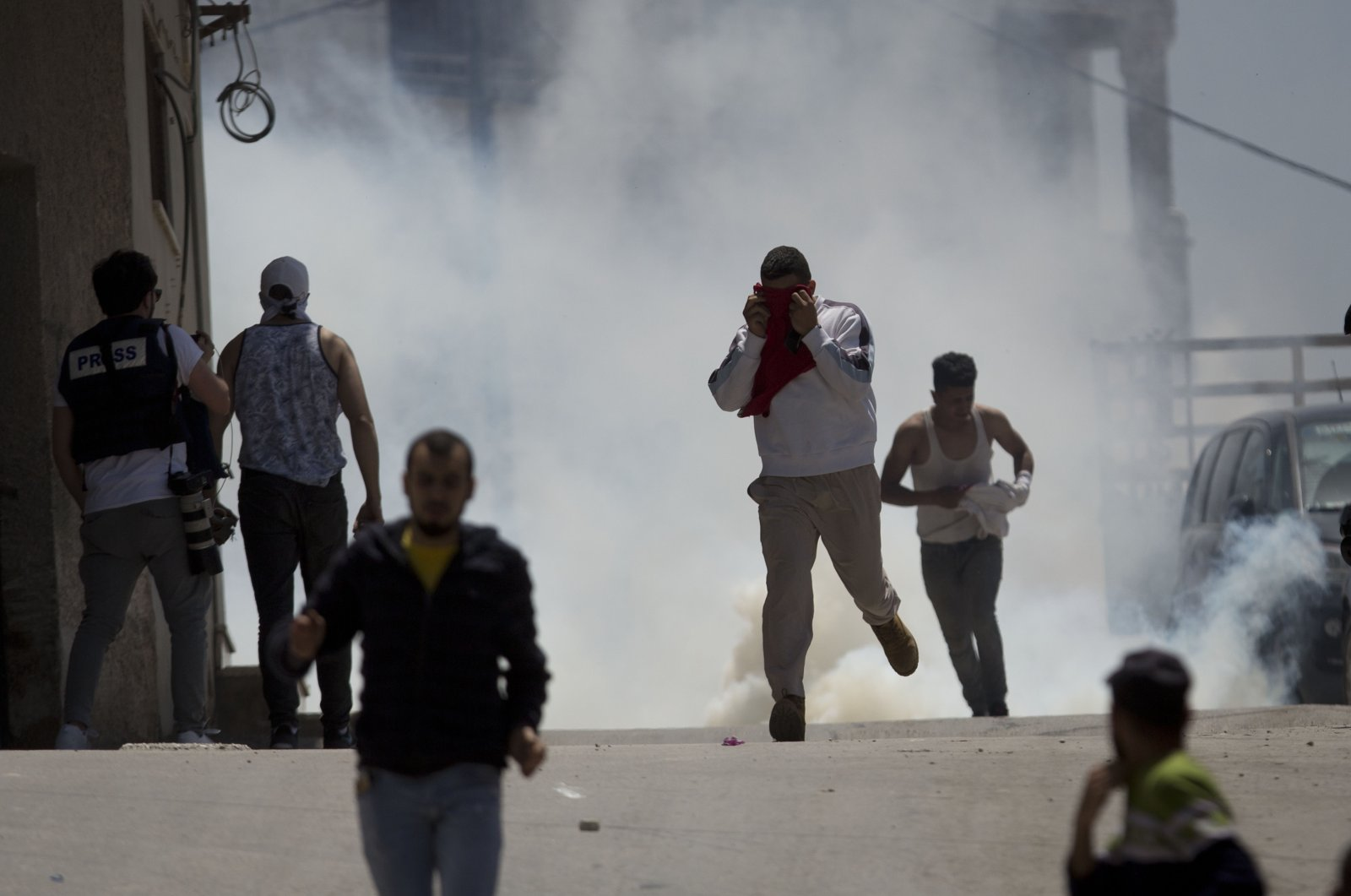 Palestinians run away from tear gas fired by Israeli soldiers in the village of Yabad near the West Bank city of Jenin, May. 12, 2020. (AP Photo)