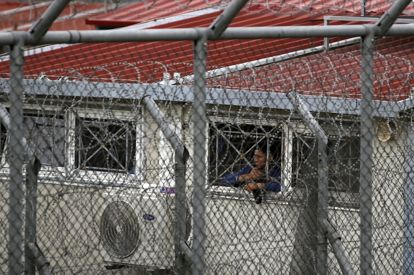 In this file photo dated Sunday, March 8, 2020, a migrant looks out from a detention center in the village of Fylakio, Evros region, near the Greek-Turkish border. (AP Photo)