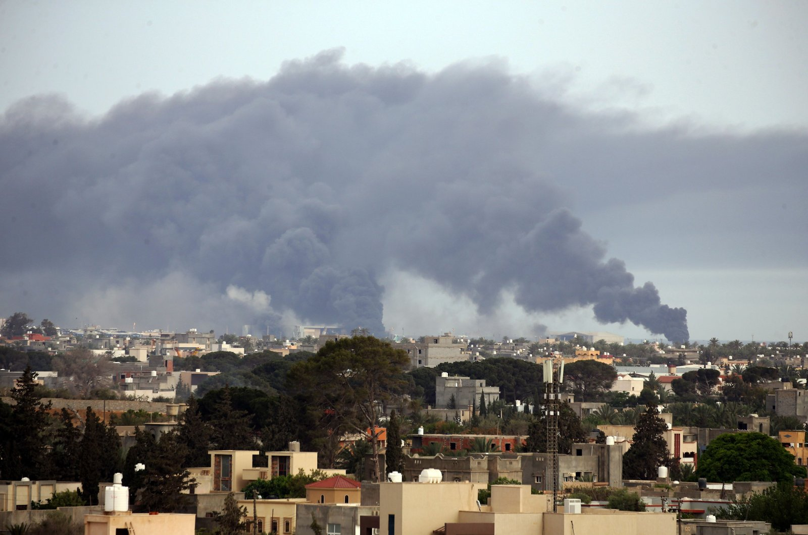 Smoke fumes rise above buildings in the Libyan capital Tripoli, during reported shelling by Khalifa Haftar's forces, on May 9, 2020. (AFP Photo)