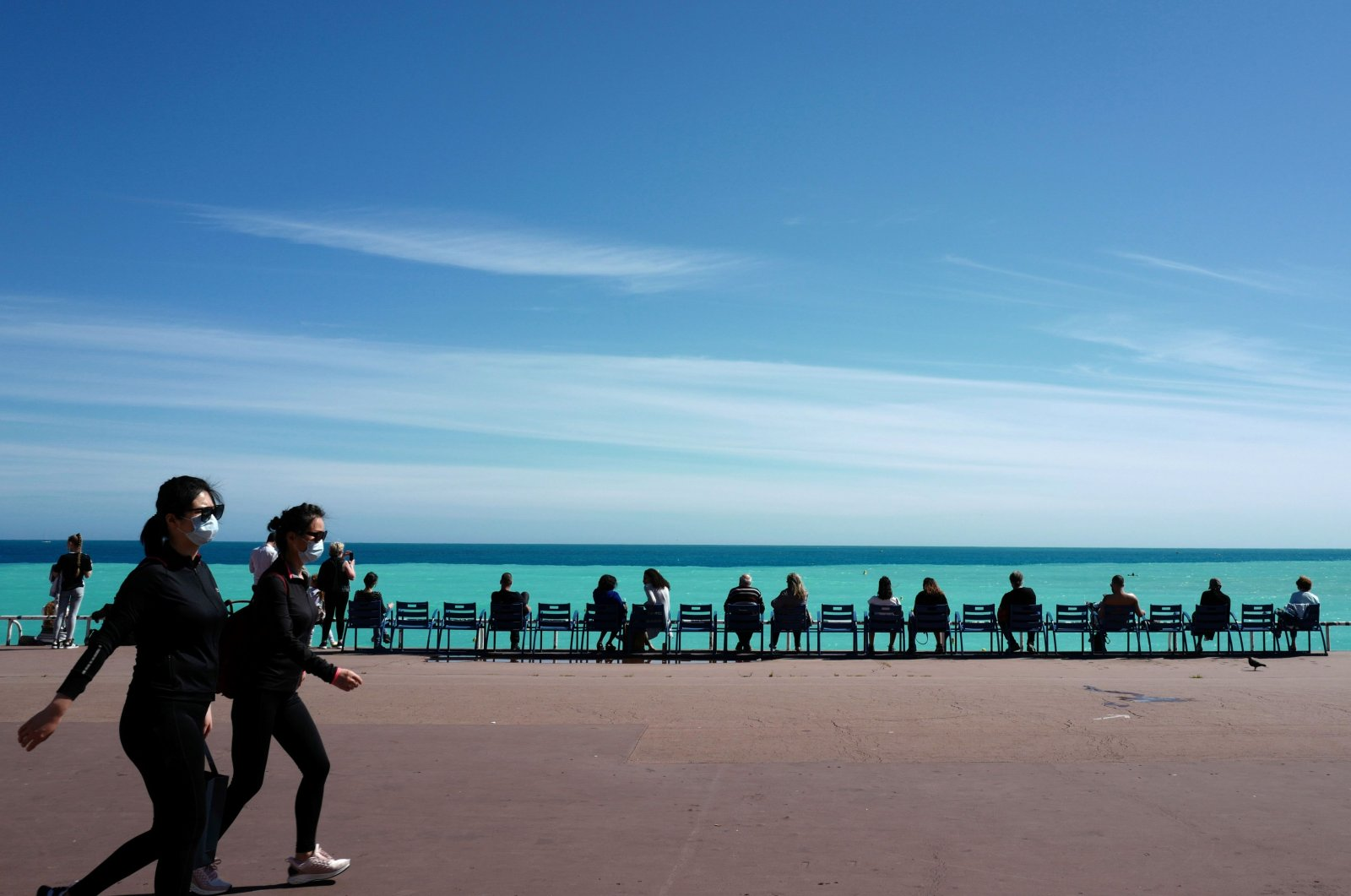"""People wearing protective facemasks walk on the """"Promenade des Anglais"""", in the French Riviera city of Nice, southern France, on May 12, 2020 on second days after France eased lockdown measures taken to curb the spread of the COVID-19. (AFP Photo)"""