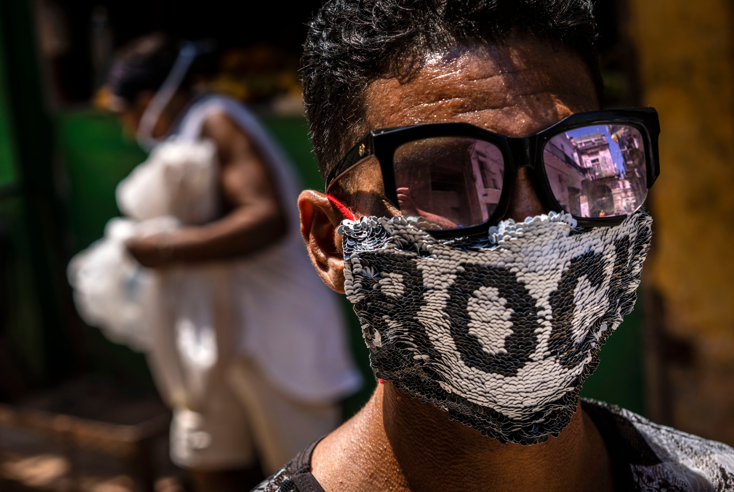 A youth wears a homemade face mask made of sequenced fabric amid the spread of the new coronavirus in Old Havana, Cuba, Friday, March 27, 2020. (AP Photo)