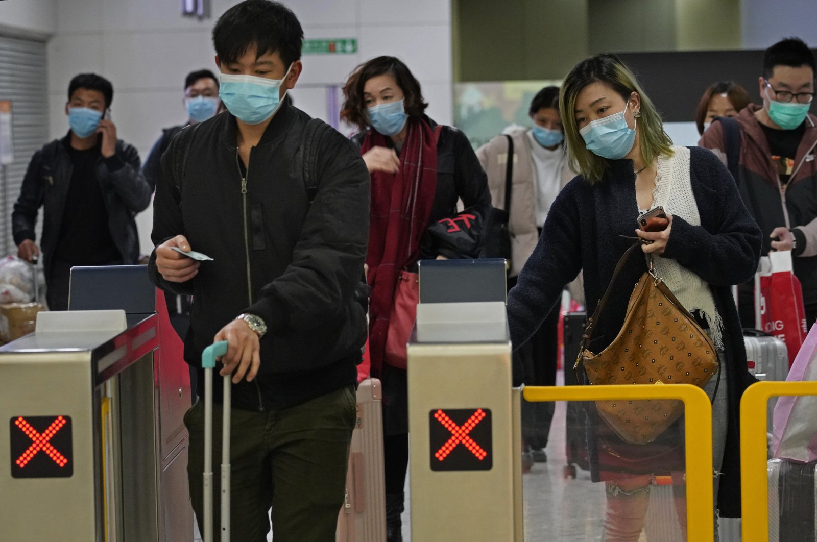 Passengers wearing protective face masks arrive at a high speed train station in Hong Kong, Jan. 28, 2020. (AP Photo)