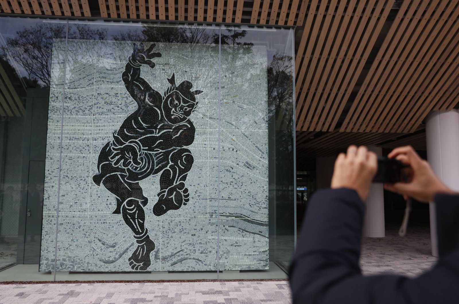 A man takes pictures of a mosaic-tile mural depicting legendary sumo wrestler, Nomino Sukune, at the new National Stadium Sunday, Dec. 15, 2019, in Tokyo. (AP Photo)