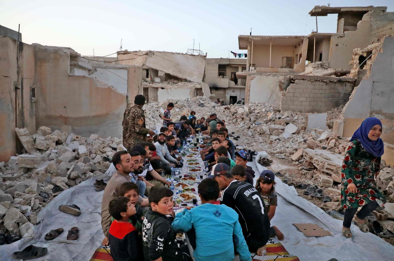 """This picture taken on May 12, 2020 in the village of Kafr Nuran in the western countryside of Syria's northern Aleppo province shows men and children seated together in the midst of ruins before starting the """"iftar"""" fast-breaking meal consumed by Muslims at sunset during the holy fasting month of Ramadan. (AFP Photo)"""