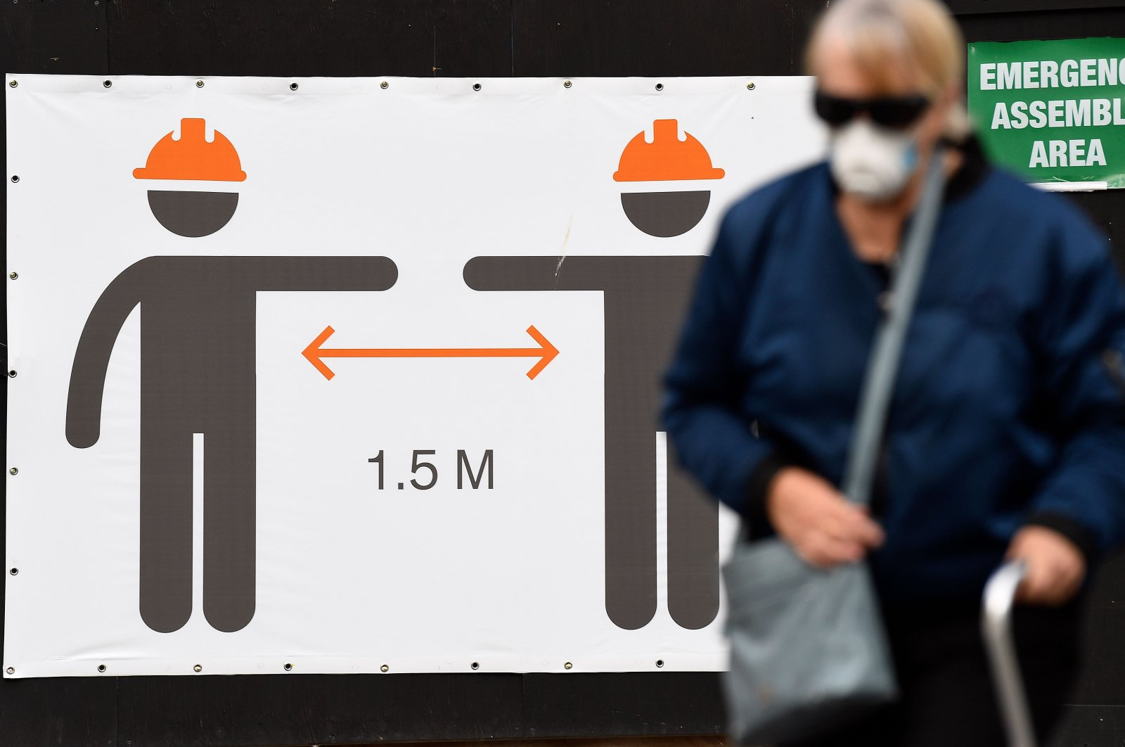 A woman wearing a face mask walks in front of a sign promoting social distancing measures, Sydney, May 13, 2020. (AFP Photo)