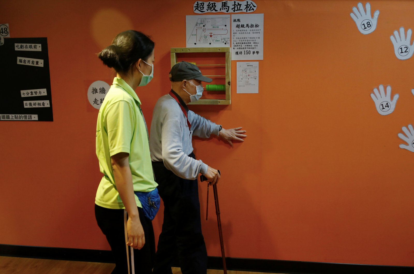 A senior wears a mask to protect himself from coronavirus disease (COVID-19) while walking along a wall at an elderly day care center in Taipei, Taiwan May 8, 2020. Picture taken May 8, 2020. (Reuters Photo)