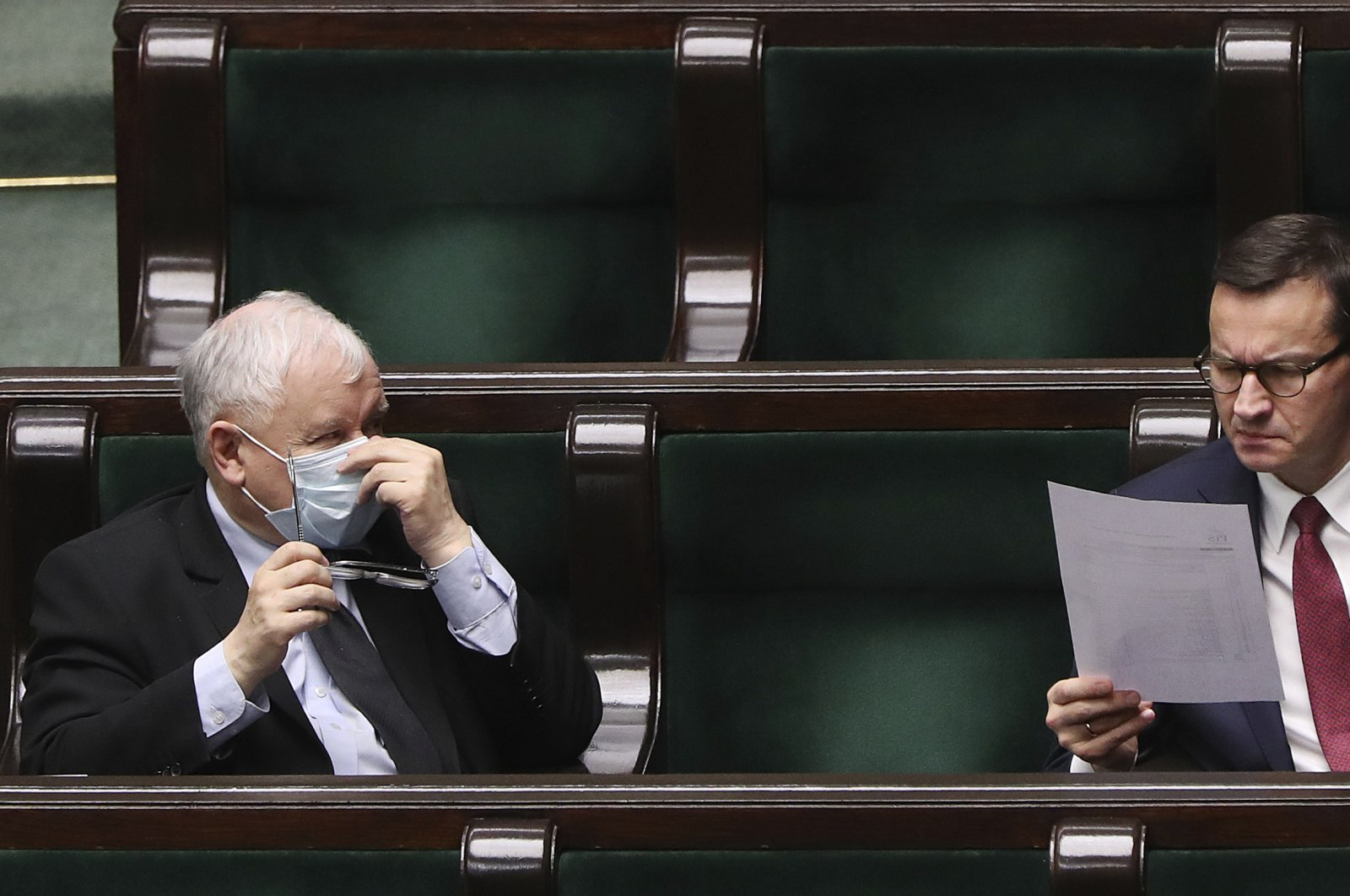 Poland's main ruling party leader Jaroslaw Kaczynski, left, wearing a mask for protection against the coronavirus and Polish Prime Minister Mateusz Morawiecki, right, work in parliament on new legislation that is to ensure the health and safety of the postponed presidential election to be held this summer, in Warsaw, Poland, Tuesday, May 12, 2020. (AP Photo)