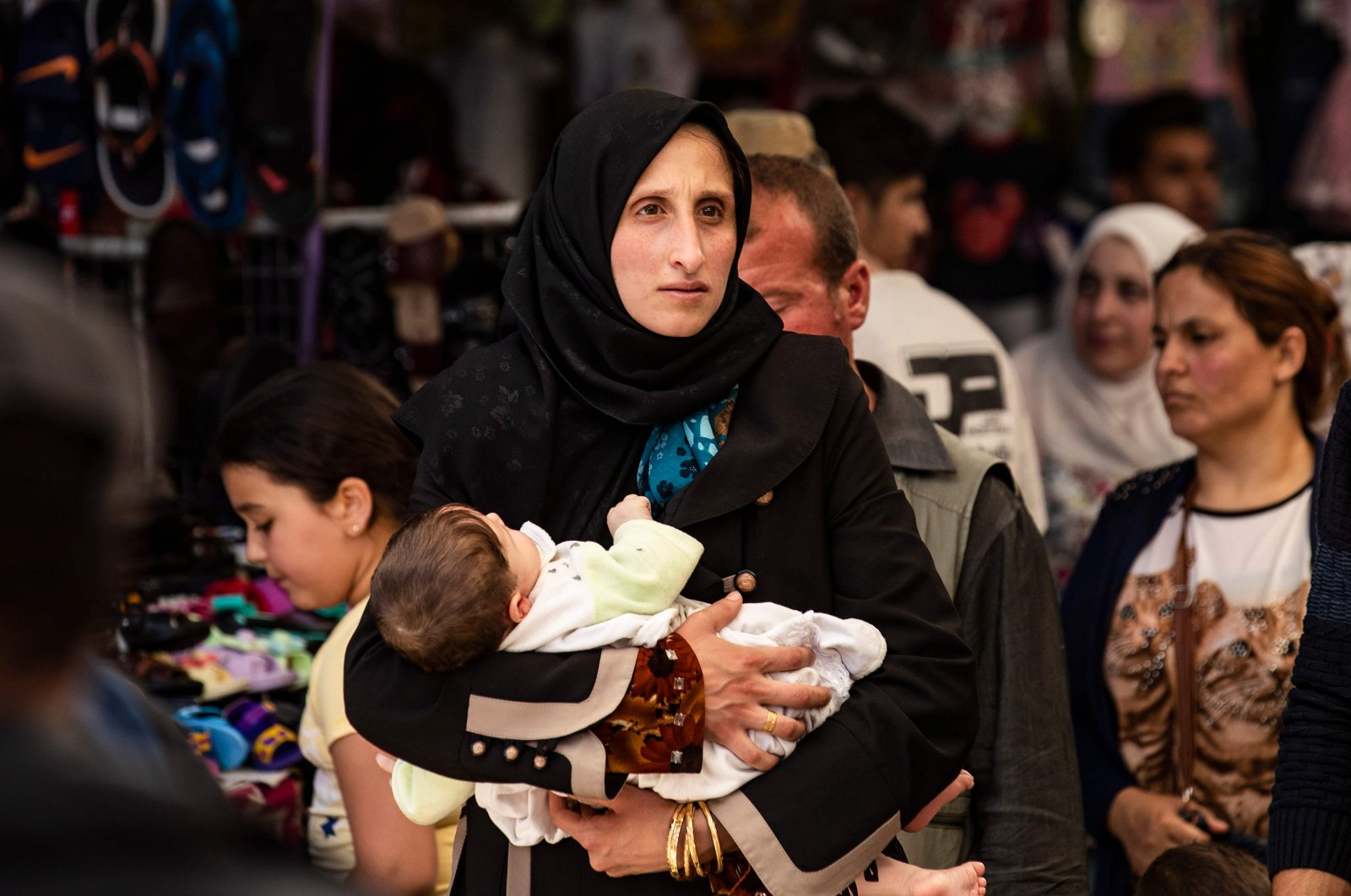 A woman walks with a baby at the main market of the city of Qamishli in Syria's northeastern Hasakah province, May 12, 2020. (AFP Photo)