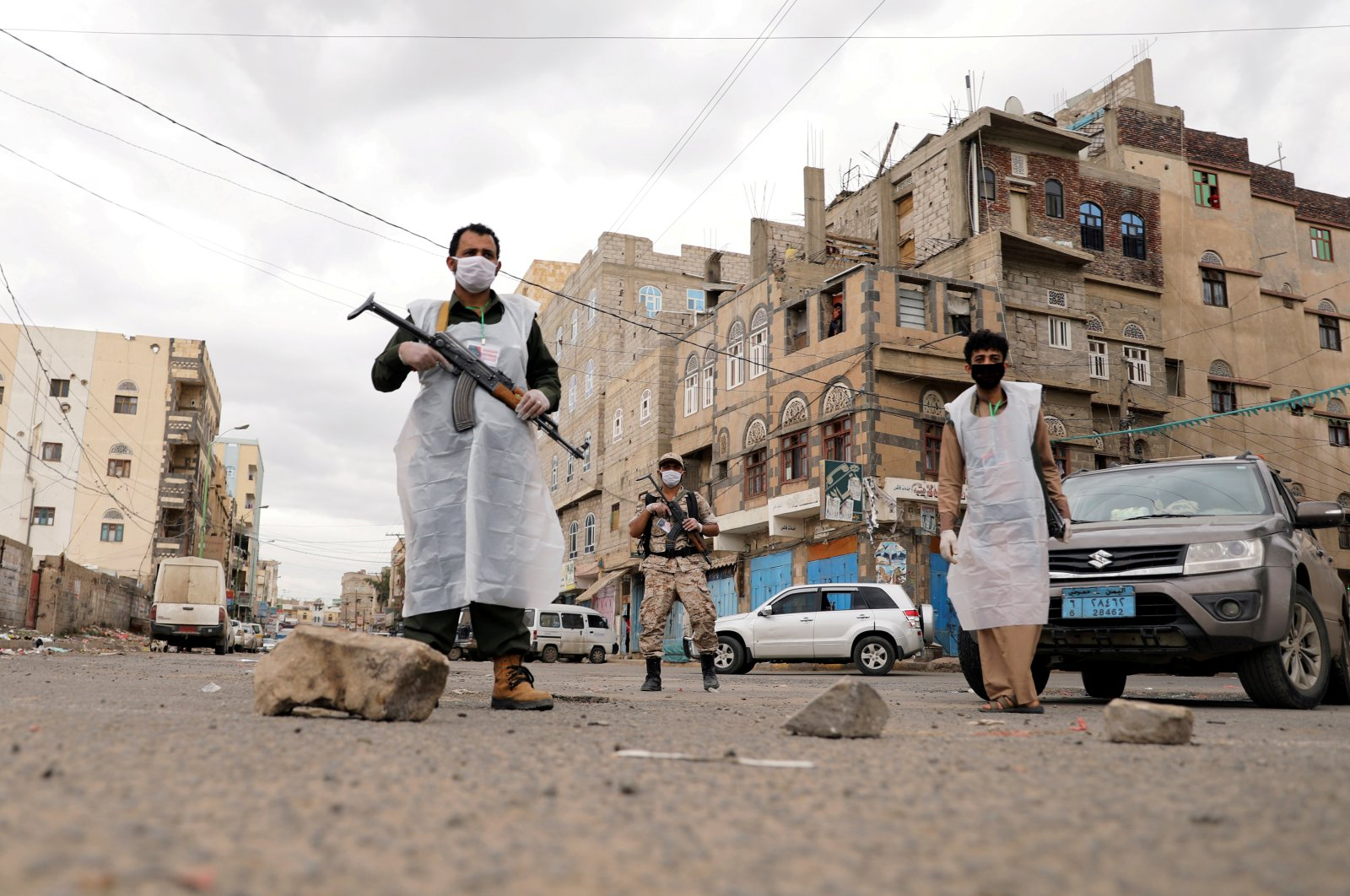 Security men wearing protective masks stand on a street during a 24-hour curfew amid concerns about the spread of the coronavirus, in Sanaa, Yemen, May 6, 2020. (REUTERS)