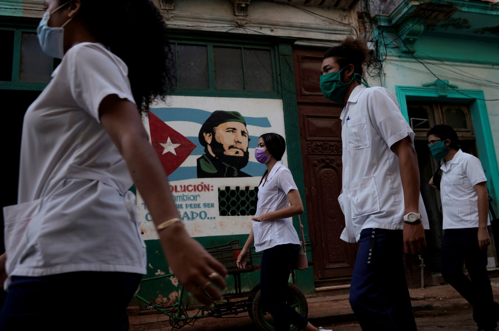 Medical students walk past an image of late Cuban President Fidel Castro in downtown Havana, Cuba, May 12, 2020. (Reuters Photo)