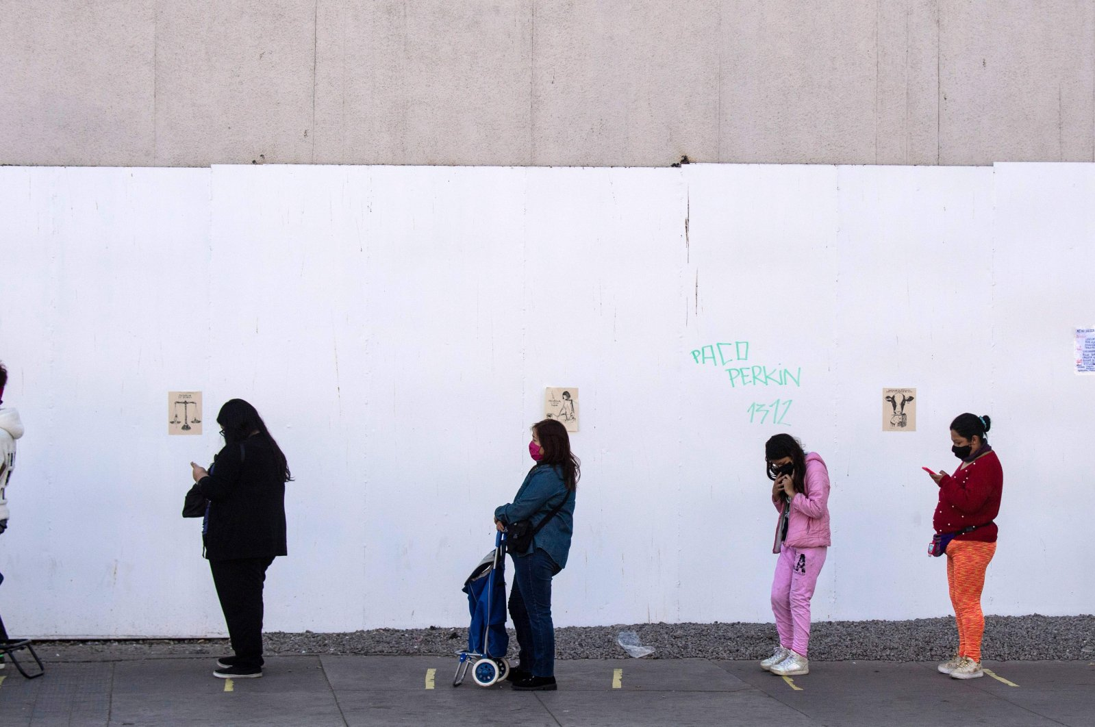 People practice social distancing as they queue outside a supermarket in Santiago, Chile, May 13, 2020. (AFP Photo)