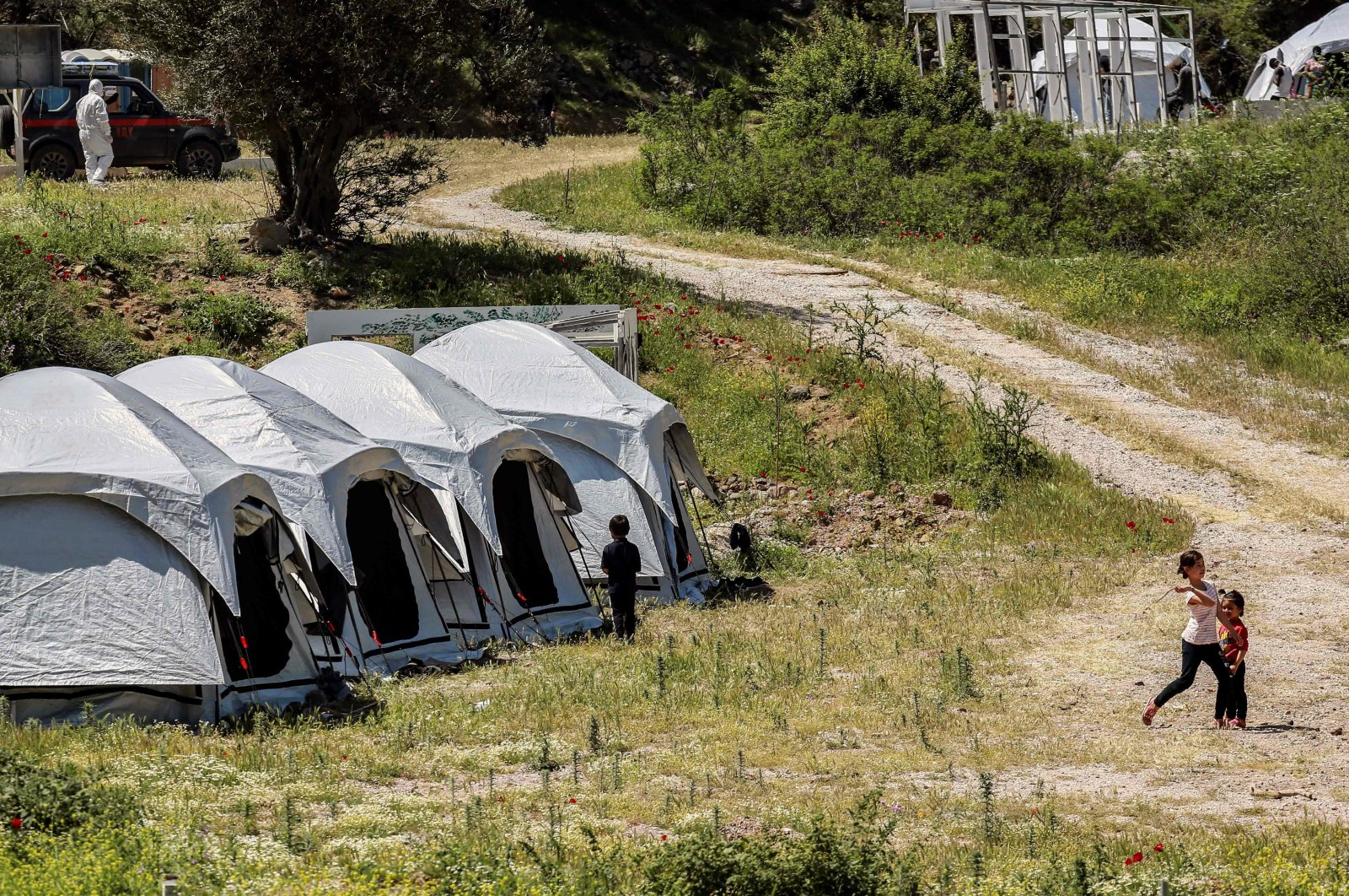 Children play outside the tents at a migrant and refugee camp where cases of COVID-19 were detected, on the Greek island of Lesbos, on May 13, 2020, as the country faces the novel coronavirus pandemic. (AFP Photo)